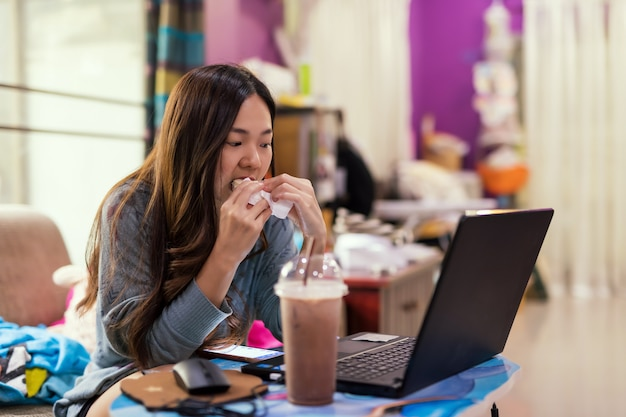 La ragazza occupata mangia il panino e lavora al computer