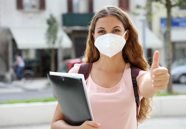 La ragazza ottimista dell'allievo torna a scuola con la maschera protettiva mostra il pollice in su