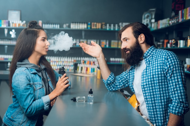 La ragazza parla con l'uomo alto venditore con i capelli lunghi e la barba.
