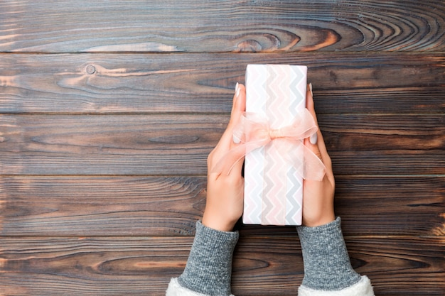 La ragazza passa il contenitore di regalo della carta del mestiere della tenuta come regalo per il natale o l'altra festa sulla vista di legno e superiore scura con lo sppace della copia