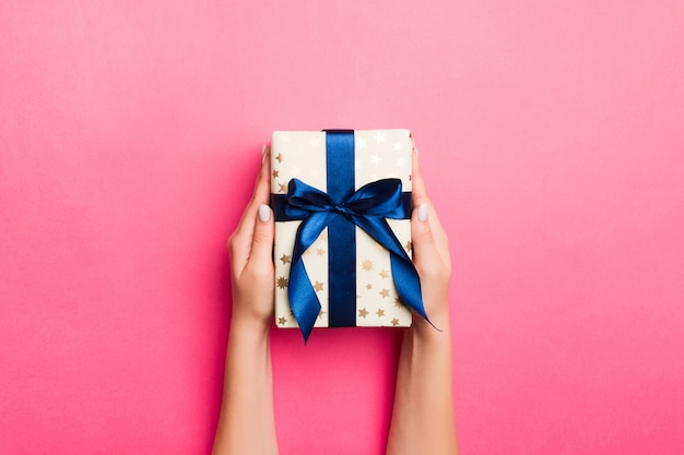 La ragazza passa il contenitore di regalo della carta del mestiere della tenuta con come regalo per il natale o l'altra festa su fondo rosa