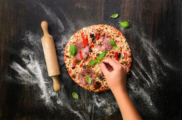 La ragazza passa la fabbricazione, decopating, preparante la pizza con le foglie del basilico su buio. vista dall'alto, copia spazio