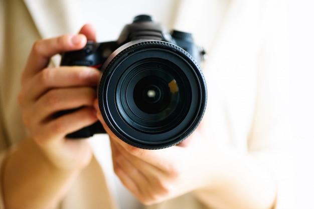La ragazza passa la macchina fotografica della tenuta della tenuta, il fondo bianco, spazio della copia. viaggia e spara al concetto