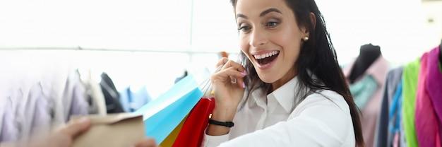 La ragazza piacevole si rallegra mentre tiene i sacchetti della spesa