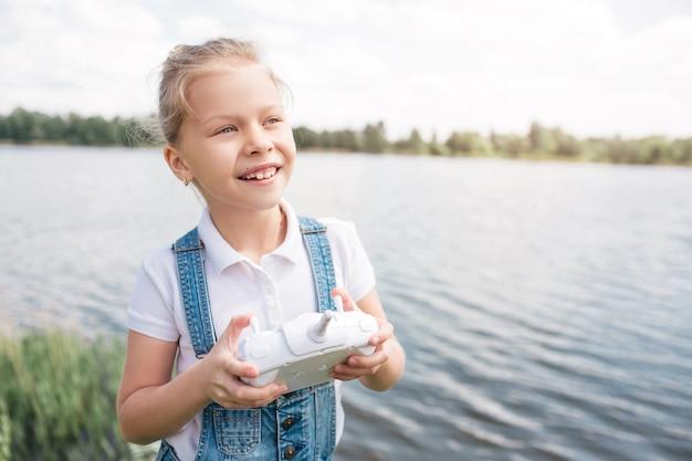 La ragazza piccola e carina sta guardando dritto e tenendo in mano il pannello di controllo bianco. lei è in piedi sul bordo dell'acqua. il bambino sembra felice.