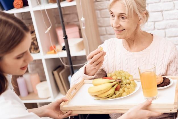 La ragazza porta la colazione sul vassoio. la donna sta mangiando