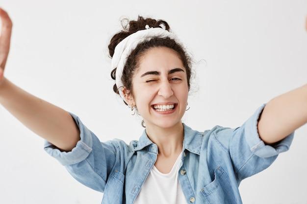 La ragazza positiva con capelli scuri e mossi in panino allunga le sue braccia, sbatte le palpebre con gioia, sorride felicemente. la donna gioisce della sua vita, ha buon umore, posa al chiuso