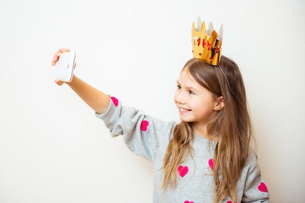 La ragazza positiva del bambino prende un selfie con una corona sulla sua testa