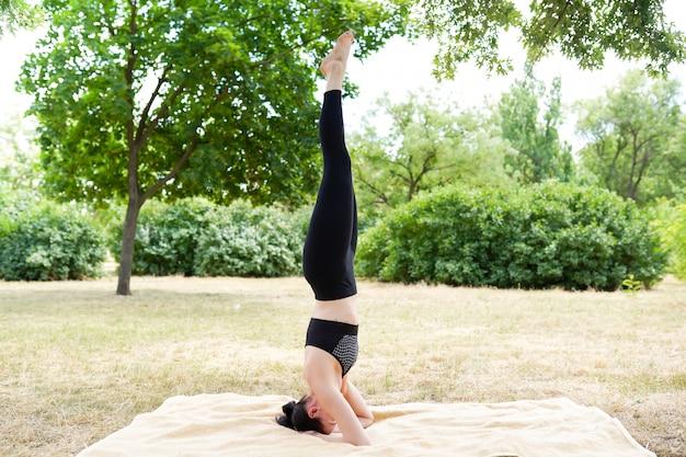La ragazza pratica yoga e medita, sfondo di natura con spazio di copia, stile di vita sano
