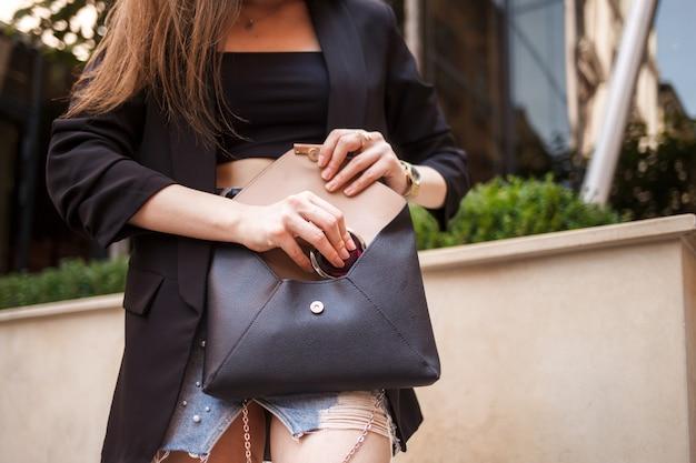 La ragazza prende lo specchietto tascabile dalla borsa. la giovane donna alla moda estrae uno specchio cosmetico da una borsa