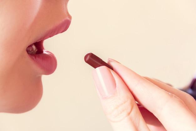 La ragazza prende una pillola con la bocca