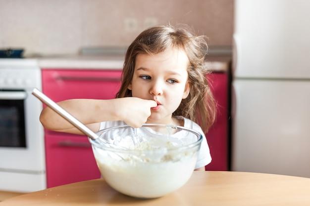 La ragazza prepara la colazione, cuocere al forno, mescolare in una ciotola di farina, latte, uova, frittelle, i bambini aiutano la madre, la famiglia colazione, cucina