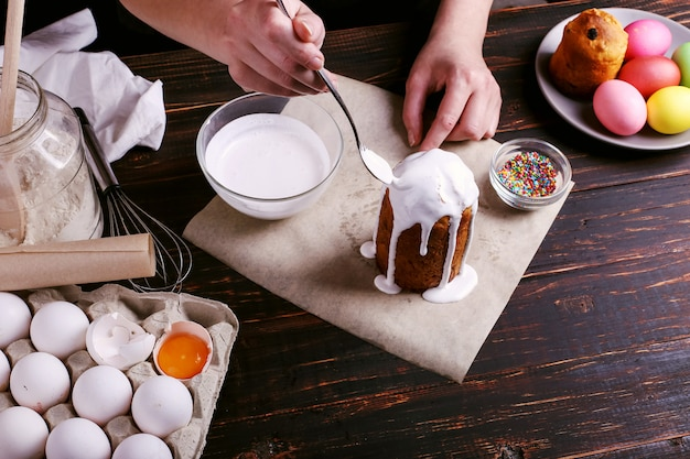 La ragazza prepara la cottura pasquale, spalma la torta con glassa e spruzza con polvere colorata. prepararsi per le vacanze sul tavolo della cucina al buio.