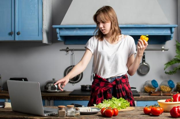 La ragazza prepara un'insalata vegetariana in cucina e guarda in un computer portatile, impara a cucinare con un video tutorial, preparando cibo sano