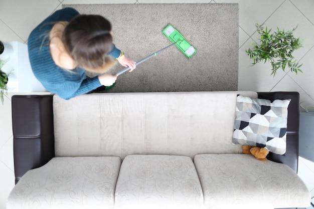 La ragazza pulisce con cura il pavimento in appartamento, vista dall'alto