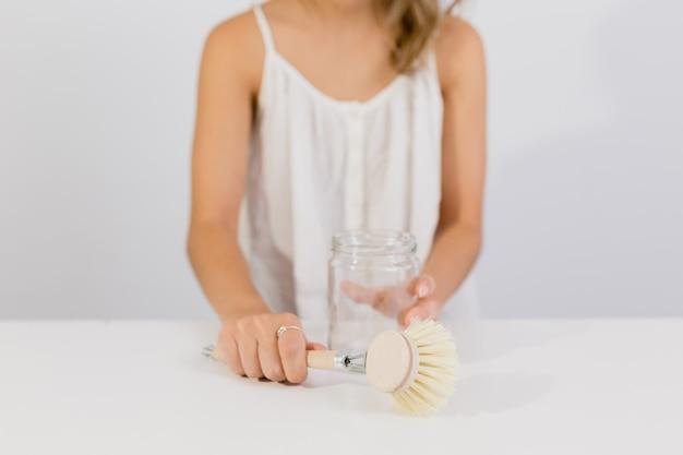 La ragazza pulisce una scatola metallica con la spazzola di legno