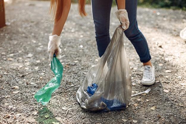 La ragazza raccoglie l'immondizia nei sacchetti di immondizia in parco