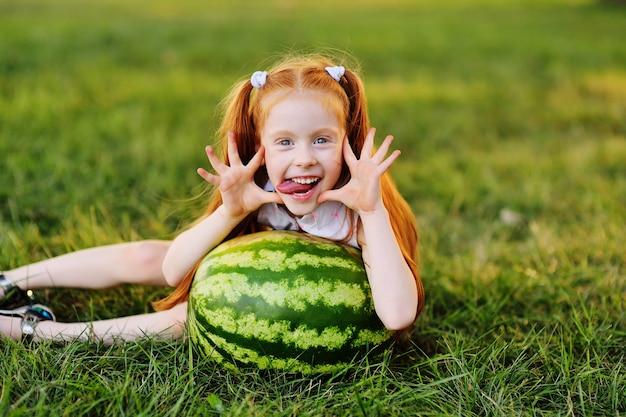La ragazza redheaded con l'anguria fa smorfie e sorride sedendosi sull'erba nel parco