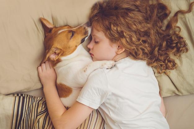La ragazza riccia dolce e il cane di jack russell sta dormendo nella notte.