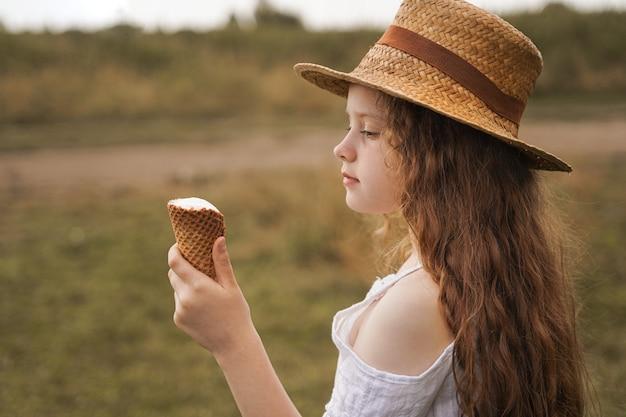 La ragazza riccia in un cappello di paglia mangia il gelato nel villaggio di estate