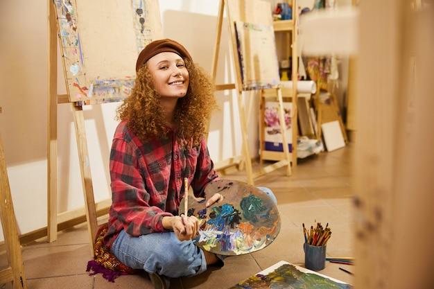 La ragazza riccia si siede su un pavimento, sorride e tiene una tavolozza con oli
