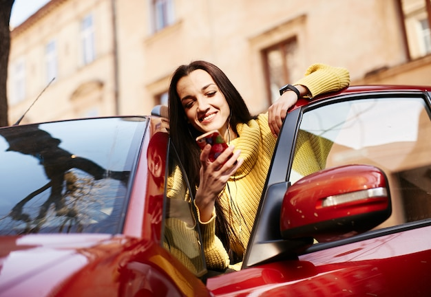 La ragazza ride e si siede in macchina