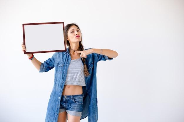 La ragazza risoluta punta il dito verso un cartello bianco bianco o un poster