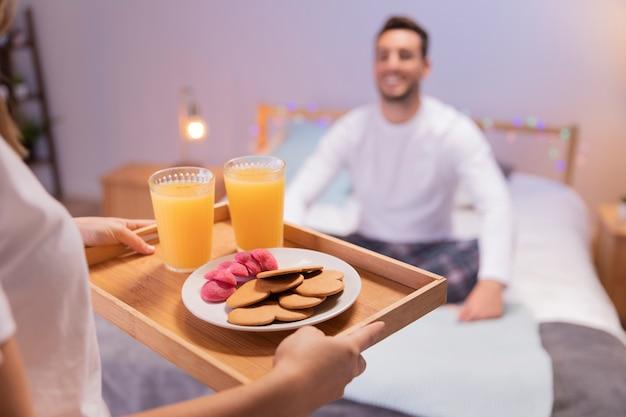 La ragazza romantica porta la colazione a suo marito