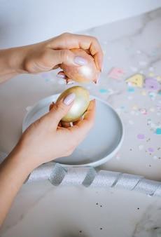 La ragazza rompe le uova di pasqua dorate su fondo di marmo, coriandoli, scintillii, nastri.
