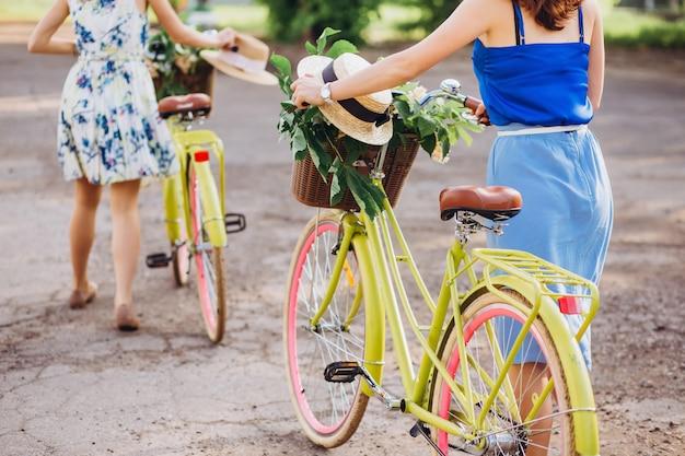 La ragazza rotola la bici. cappello di paglia in un cestino della bicicletta. giro in bici estivo.