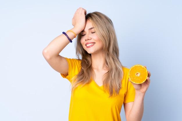 La ragazza russa dell'adolescente che tiene un'arancia sulla parete blu ha realizzato qualcosa e intende la soluzione