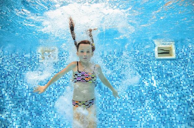 La ragazza salta e nuota in piscina sott'acqua
