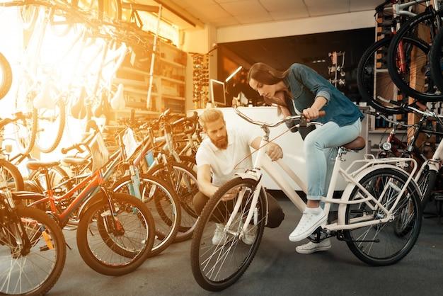 La ragazza sceglie city bike con il venditore nel negozio di articoli sportivi.