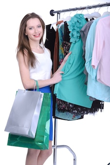 La ragazza sceglie il vestito isolato su bianco.