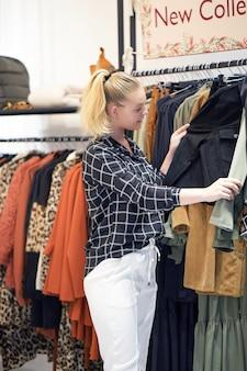 La ragazza sceglie le cose in un negozio di abbigliamento