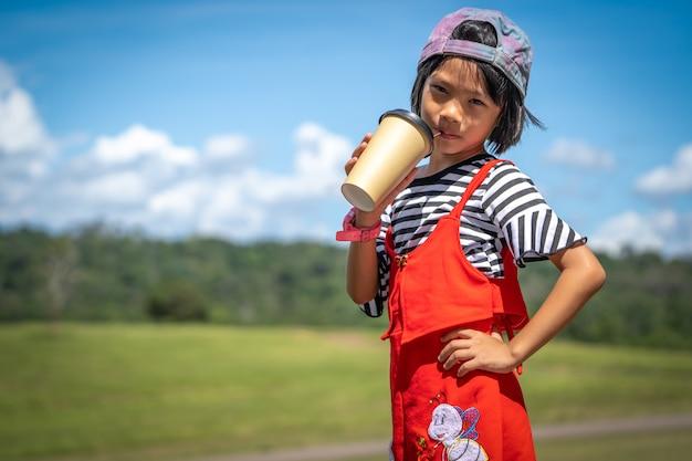 La ragazza scherza il gioco e l'acqua potabile dalla tazza di carta su all'aperto della natura del pascolo del pascolo