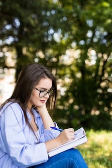 La ragazza seria dai capelli scuri sorridente in giacca di jeans e occhiali scrive in taccuino nel parco
