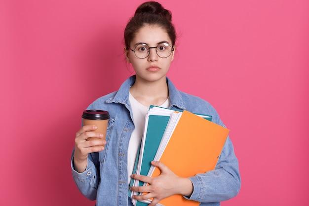 La ragazza seria dello studente con la cartella di carta e porta via il caffè in mani