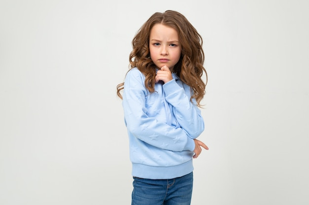 La ragazza seria in una felpa con cappuccio blu casuale sta con un'espressione onesta su una parete bianca con spazio
