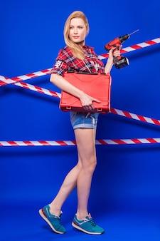 La ragazza sexy attraente del costruttore in camicia chechered rossa, pantaloncini di jeans e snickers tiene il cacciavite e la cassetta portautensili