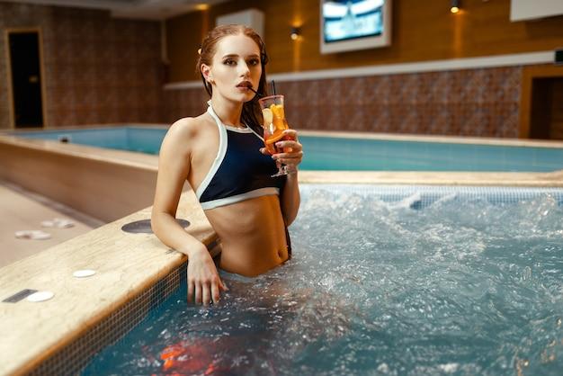 La ragazza sexy beve il cocktail di frutta a bordo piscina