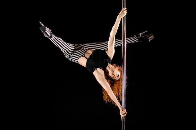 La ragazza sexy di pole dance si esercita e posa sul pilone