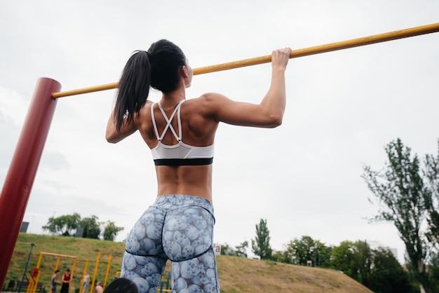 La ragazza sexy è tirata su su una barra orizzontale all'aperto. fitness. uno stile di vita sano