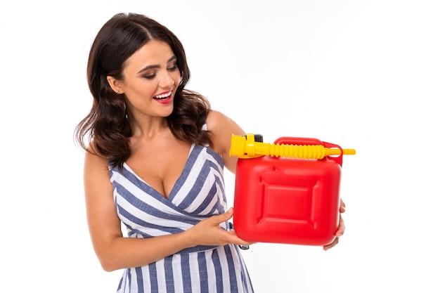 La ragazza sexy in un vestito tiene una scatola metallica rossa con benzina del combustibile su bianco con lo spazio della copia