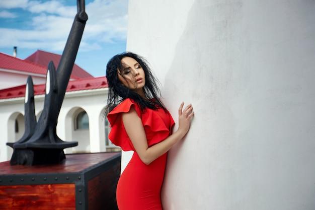 La ragazza sexy in vestito rosso sta vicino al faro un giorno di estate soleggiato