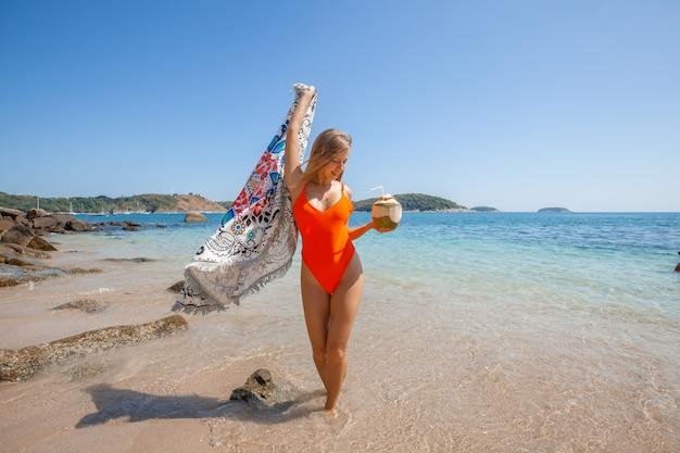 La ragazza sexy si diverte sulla spiaggia con cocco fresco e panno di spiaggia