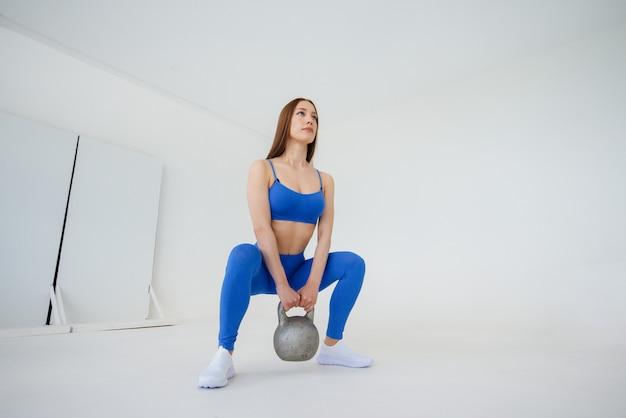 La ragazza sexy si esercita con un peso in una tuta sportiva blu su una parete bianca. fitness, stile di vita sano.