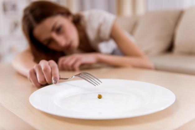 La ragazza sfinita dalla malnutrizione si trova sul divano.