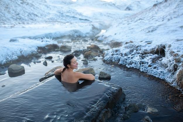 La ragazza si bagna in una sorgente termale all'aperto con una splendida vista sulle montagne innevate. incredibile islanda in inverno