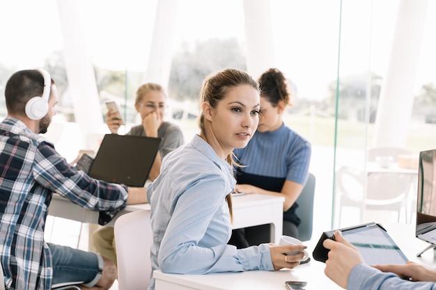 La ragazza si è girata davanti ad una tabella con altre persone che lavorano in un coworking